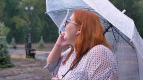 Het emotionele vette gembermeisje met glazen bevindt zich onder regen in park, die op telefoon spreken, houdend paraplu, mededeli stock videobeelden