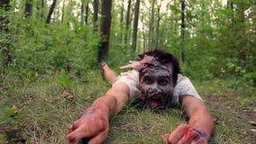 Het enge zombiemonster kruipt door het gras en de holding een mes stock video