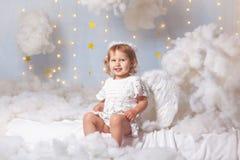 Het engelenkind zit de wolken neer kijkt stock afbeelding