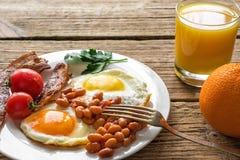 Het Engelse ontbijt diende in een plaat met gebraden ei, bonen, tomaten en bacon met vers jus d'orange Stock Afbeeldingen