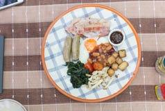 Het Engelse ontbijt op een lijst met gebraden ei, gebakken bonen, braadde aardappels, bacon, tomaat, worsten, paddestoel, barbecu stock foto
