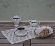 Het Engelse theekopje met schotel, de roomkruik, de suikerkom en een cake werpen met koekjes, het fijne porselein van beenchina,  stock afbeeldingen