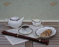 Het Engelse theekopje met schotel, de theepot, de roomkruik en een cake werpen, het fijne porselein van beenchina, en een blokflu royalty-vrije stock afbeelding