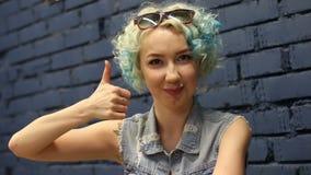 Het enthousiaste gemotiveerde aantrekkelijke jonge vrouw geven duimen op gebaar van goedkeuring en succes stock videobeelden