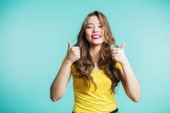 Het enthousiaste gemotiveerde jonge vrouw geven duimen op gebaar Mooi donkerbruin meisje die in gele t-shirt en rode lippen broa  stock afbeelding