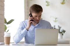 Het ernstige arbeider het spreken telefonisch bekijken laptop het scherm royalty-vrije stock foto