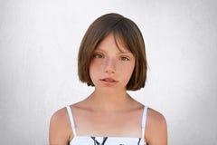 Het ernstige freckled meisje met bobbed haar en donkere die ogen direct kijkend in camera, over witte achtergrond wordt geïsoleer royalty-vrije stock afbeelding