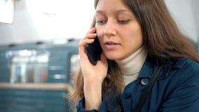 Het ernstige jonge vrouw spreken op de telefoon en krijgt op de trein in de metro stock footage