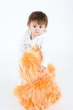 Het ernstige kijken meisje dat zich met grote sinaasappel bevindt furr Stock Fotografie