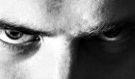 Het ernstige kwaad, boos, ogen, kijkt mens, die de camera, zwart-wit portret onderzoeken royalty-vrije stock afbeelding