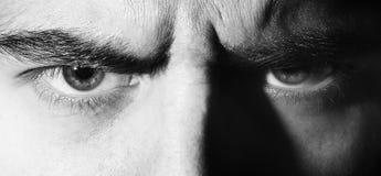 Het ernstige kwaad, boos, ogen, kijkt mens, die de camera, zwart-wit portret onderzoeken stock fotografie