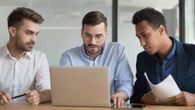 Het ernstige mannelijke werknemerswerk aangaande laptop samen op vergadering stock foto's