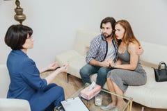 Het ernstige paar zit samen en omhelst elkaar Zij bekijken psycholoog Doctor spreken aan hen stock foto