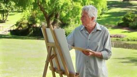 Het ernstige rijpe mens schilderen op een canvas stock video