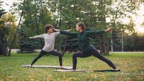 Het ervaren instructeurs slanke meisje onderwijst haar vrouwelijke de yogaasanas van studentenhatha op warme de herfstdag in stad stock videobeelden