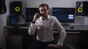 Het ervaren softwareontwikkelaar glimlachen die op zijn smartphone spreken terwijl computers op de achtergrond om groot te behand stock footage