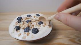 Het eten van bosbessen met room of yoghurt door lepel stock video