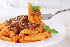 Het eten van de deegwaren van de sausnoedels van Penne Rigate Bolognese of Bolognaise- Royalty-vrije Stock Foto's
