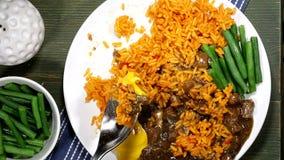 Het eten van een Maaltijd van de Slabonen van Rundvleesstew and tomato rice with stock videobeelden