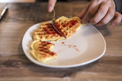 Het eten van Eigengemaakte wafels op witte plaat met de rode gelei van de aardbeijam Royalty-vrije Stock Afbeeldingen
