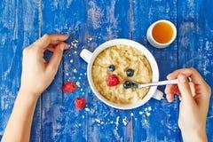 Het eten van havermoutpap en bessen met honing Royalty-vrije Stock Fotografie