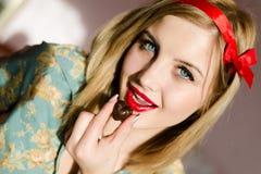 Het eten van jonge vrouw van chocolade de mooie pinup stock foto's