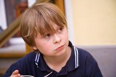 Het eten van jongen kijkt verbaasd Stock Foto's