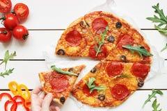 Het eten van pizza, hoogste mening Hand die plak van hete delisious pizza op de witte houten lijst nemen Royalty-vrije Stock Foto's