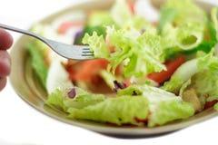Het eten van salade met vork Stock Foto