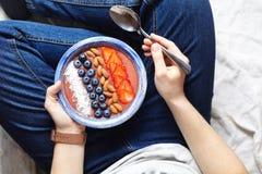 Het eten van smoothies ontbijtkom Yoghurt, aardbei, bosbes, zaden, kokosnoot, verse en droge vruchten in blauwe ceramisch royalty-vrije stock foto
