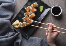 Het eten van sushibroodje op zwarte plaat Lucht mening stock afbeeldingen