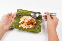Het eten van traditionele banaanblad verpakte nasi lemak Stock Foto