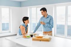 Het eten van voedsel Gelukkig Mooi Paar die Pizza binnen eten Vrije tijd C royalty-vrije stock foto