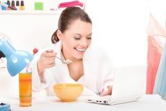 Het eten van vrouwenlaptop computer royalty-vrije stock afbeeldingen