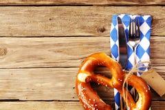 Het eten van werktuigen met een Beierse pretzel Stock Afbeelding