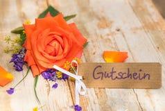 Het etiket met Duitse woord, Gutschein, middelenbon of coupon en nam voor Valentijnskaartendag of Moedersdag toe royalty-vrije stock foto's