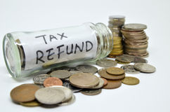 Het etiket van de belastingsterugbetaling in een glaskruik met muntstukken die uit morsen Royalty-vrije Stock Afbeelding