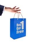 Het etiket van de verkoop op blauwe het winkelen zak ter beschikking Stock Foto