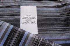 Het etiket van de wasinstructie op katoenen verticaal strepenoverhemd Royalty-vrije Stock Foto's