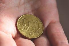 Het 50 Eurocentmuntstuk in de palm van een wijfje overhandigt A Royalty-vrije Stock Afbeeldingen