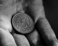 Het 50 Eurocentmuntstuk in de palm van een wijfje overhandigt B Royalty-vrije Stock Afbeelding