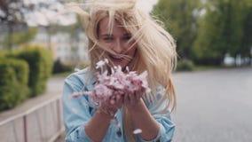 Het Europese jonge blonde aantrekkelijke meisje beweegt zich onderaan het park, dan draait zij en werpt de bloemblaadjes van kers stock video
