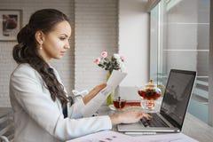 Het Europese meisje die aandachtig monitor van laptop onderzoeken werkt Royalty-vrije Stock Afbeelding