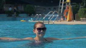 Het Europese meisje in zonnebril bespat blauw water in buitenpool op zonnige de zomerdag stock video