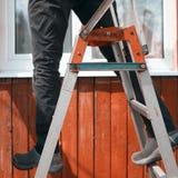 Het in evenwicht brengen op een ladder stock afbeelding