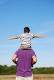 Het in evenwicht brengen van de jongen op de schouders van zijn vader Stock Foto's