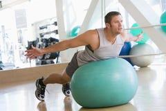 Het In evenwicht brengen van de mens op Zwitserse Bal bij Gymnastiek Stock Foto's