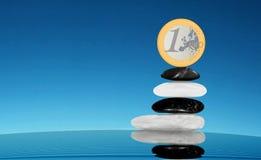 Het in evenwicht brengen van 1 EURO op stapel stenen zen Royalty-vrije Stock Foto's