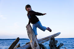 Het In evenwicht brengen van het meisje op Drijfhout bij het Strand Royalty-vrije Stock Afbeeldingen