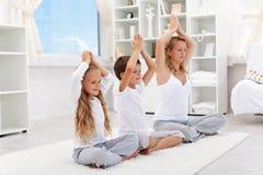 Het evenwichtige leven - vrouw die met jonge geitjes yoga doet stock foto's